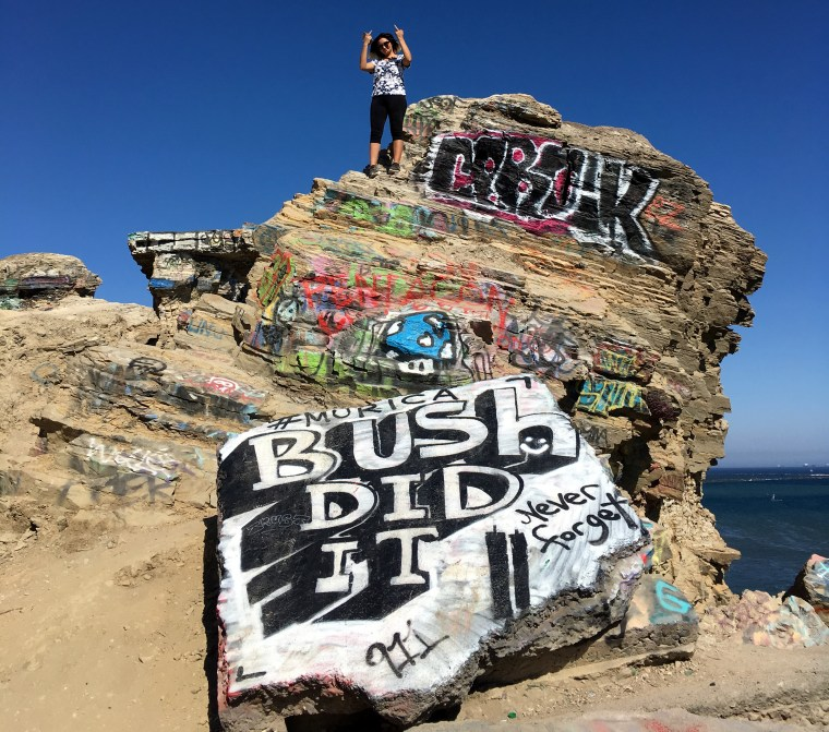 Raul's friend Laritza sanding high atop a large rock and rubble tower with lots of graffiti on it at Sunken City, San Pedro, CA