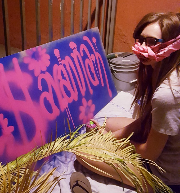 """Savannah Avalos with a bandanna over her mouth to block paint fumes, works on a spray painting of her name """"Savannah"""" in pink letters on a purple board"""