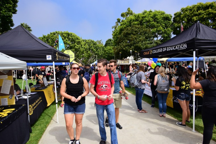 students walking through many booths from campus clubs and other organizations at CSULB