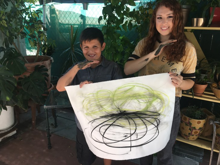 Yuliana & Omar holding a pastel drawing on paper