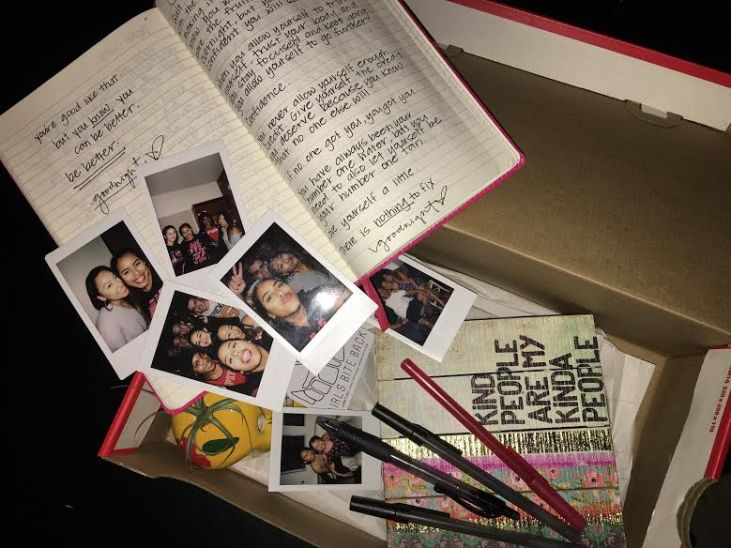 """Nike shoe box that Abigail Manuel has transformed into an """"Art Care Package"""" to her sister up in Northern California. Contents include polaroid pictures, a hand-written journal, and other ephemera"""