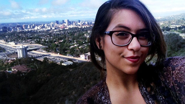 Adriana Maciel at The Getty Center in Westwood. Photo of Adriana with Westwood and Los Angeles behind her. It's a bright afternoon with rare to Los Angeles puffy white clouds hanging on the horizon