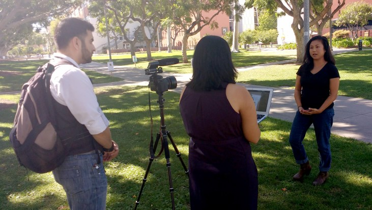Phatana Ith being interviewed by Lata Pandya and video recorded by Raul de Paz on the grass outside the CSULB HSCI building