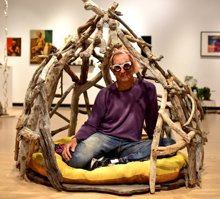 Glenn Zucman sitting inside a small, 1-person structure made of irregular tree branches forming a dome like ceiling and with a large pillow at the floor. The structure sits inside the CSULB School of Art, Gatov Gallery East as part of an SOA Art Education group exhibition