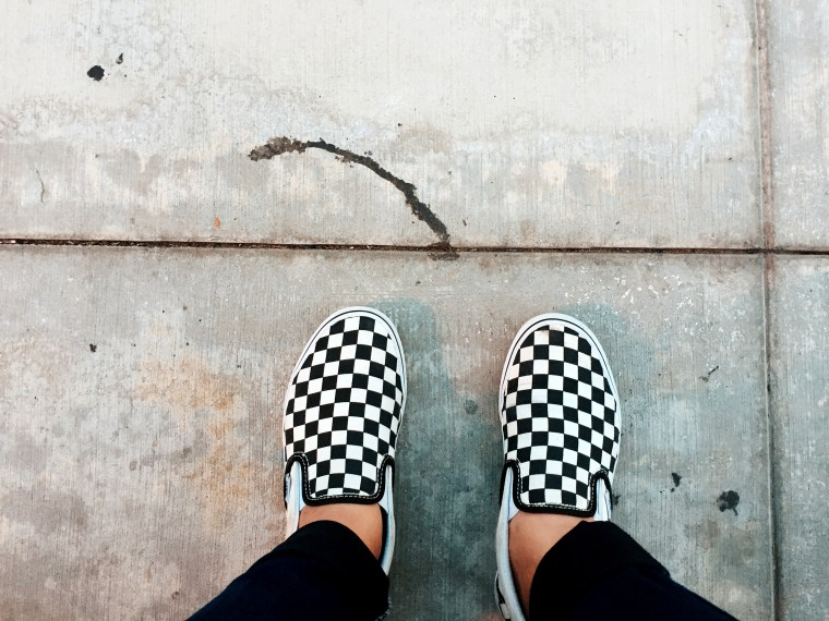 photo of Maritess Inieto's black and white checked shoes against a concrete sidewalk