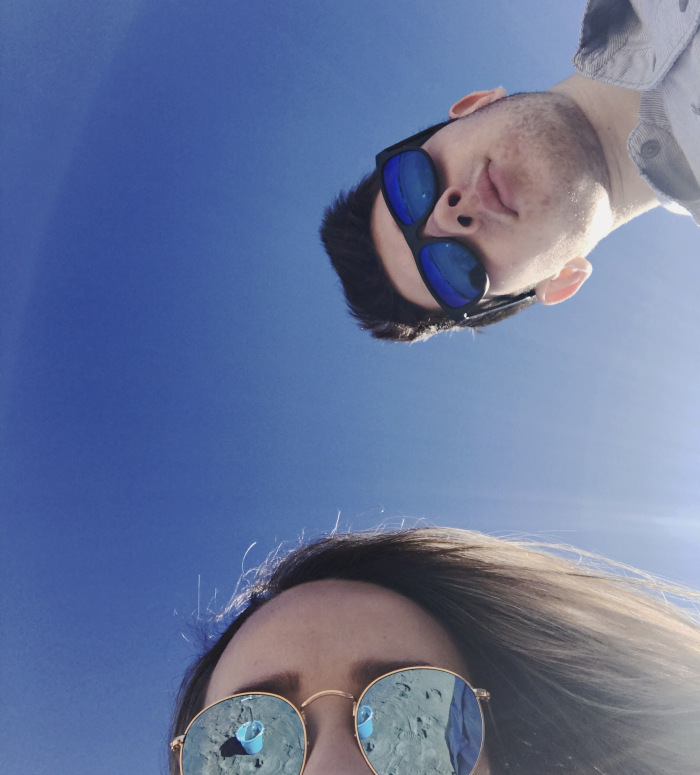 image from camera pointed up showing blue sky and the tops of 2 faces wearing mirrored sunglasses