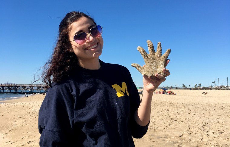 Makenna on the beach wearing heart-shaped sunglasses, smiling, and holding a plaster casting of her hand