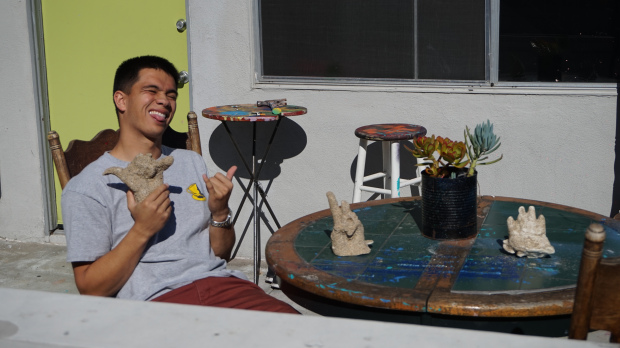 Jared sits on the patio with a number of plaster castings of his hands