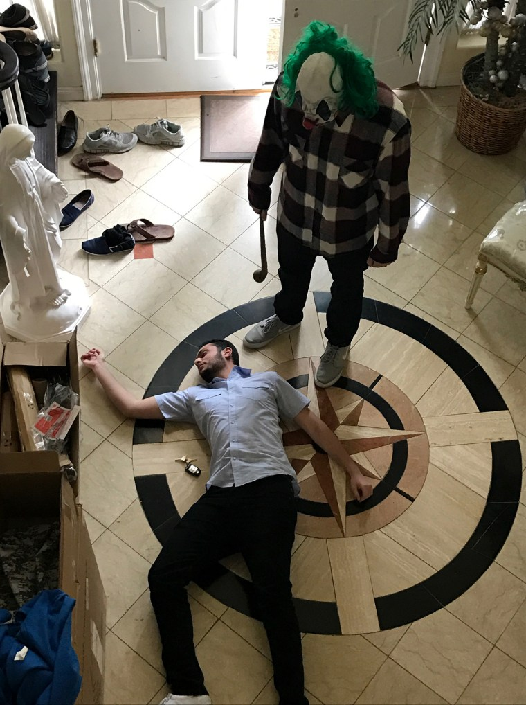 Michael lying on a large marble floor pretending to be the victim of a psycho clown