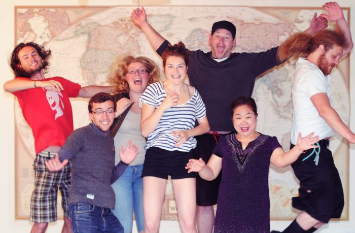 Students from 7 different countries jumping in the air in front of a large world map