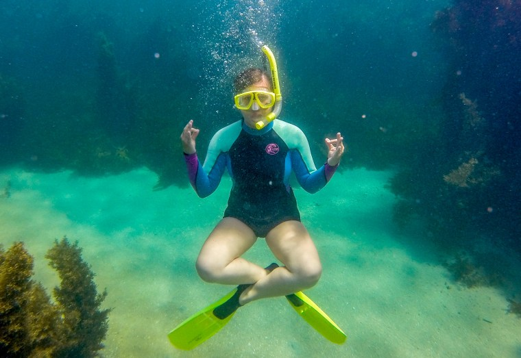 Chantae Reden in a wetsuit and with snorkel gear, underwater, in a lotus pose