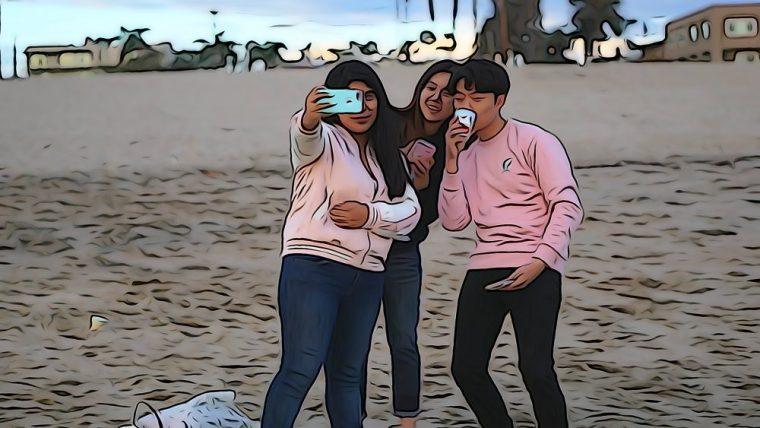 students taking a selfie on the beach
