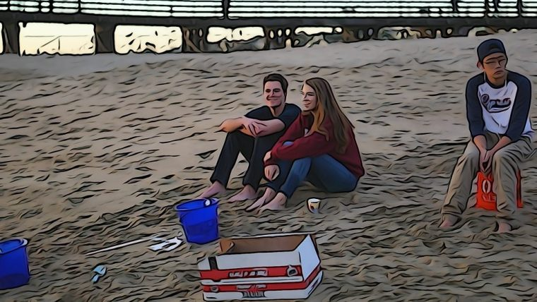 students sitting on the sand at Seal Beach