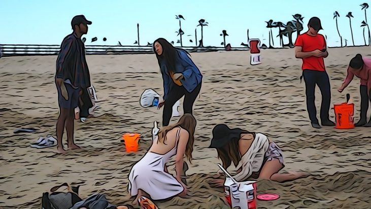 students digging plaster castings out of the sand at the Seal Beach Pier in Seal Beach, California