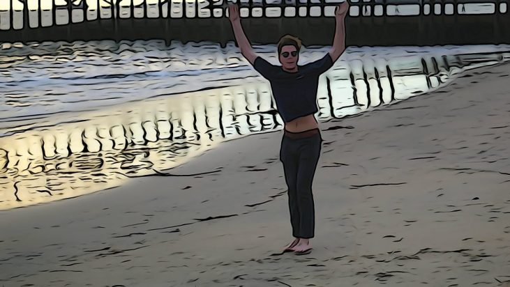student doing cartwheels on the sand at the Seal Beach Pier