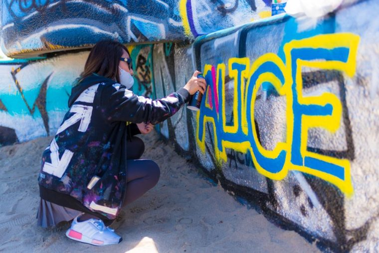 Alice Chen painting her name at the Venice Beach Art Walls