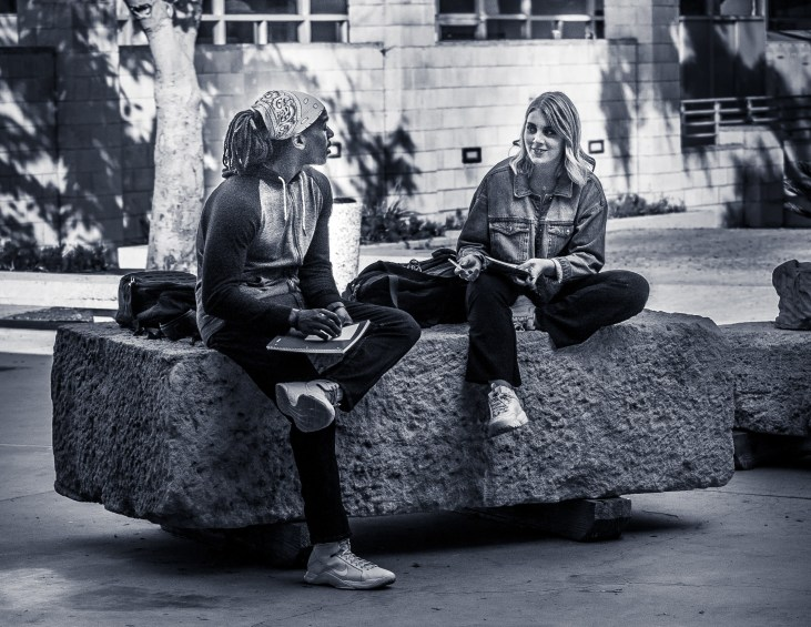 students sitting on a large stone