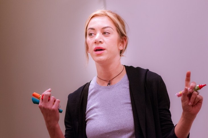 Lizzie Green holds several whiteboard markers in her hand and speaks to the class