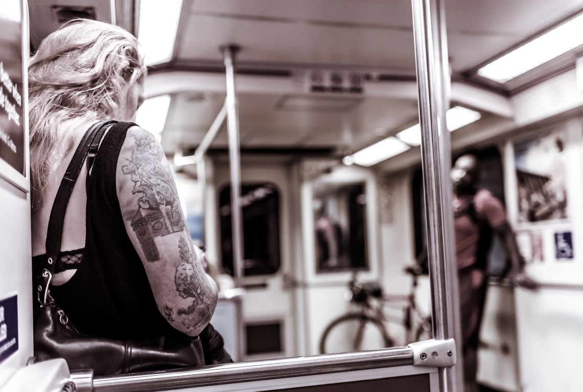 A woman riding the Metro Red Line with a large tattoo on her arm, including landscape elements of buildings and trees