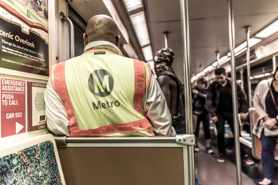 Commuters getting off the Metro Red Line at the last stop, Union Station, as a Metro employee prepares to clean the car.