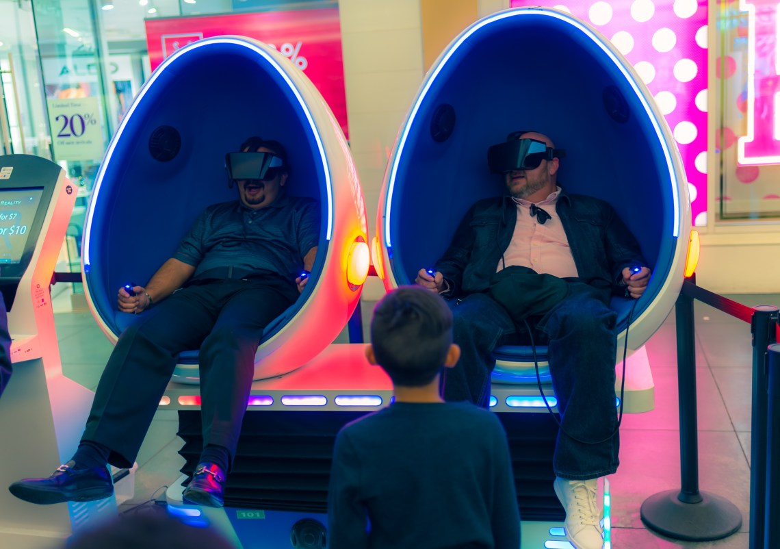 """two guys in VR pods taking a """"ride"""" at the Hollywood & Highland shopping center on Hollywood Blvd in Los Angeles, California"""