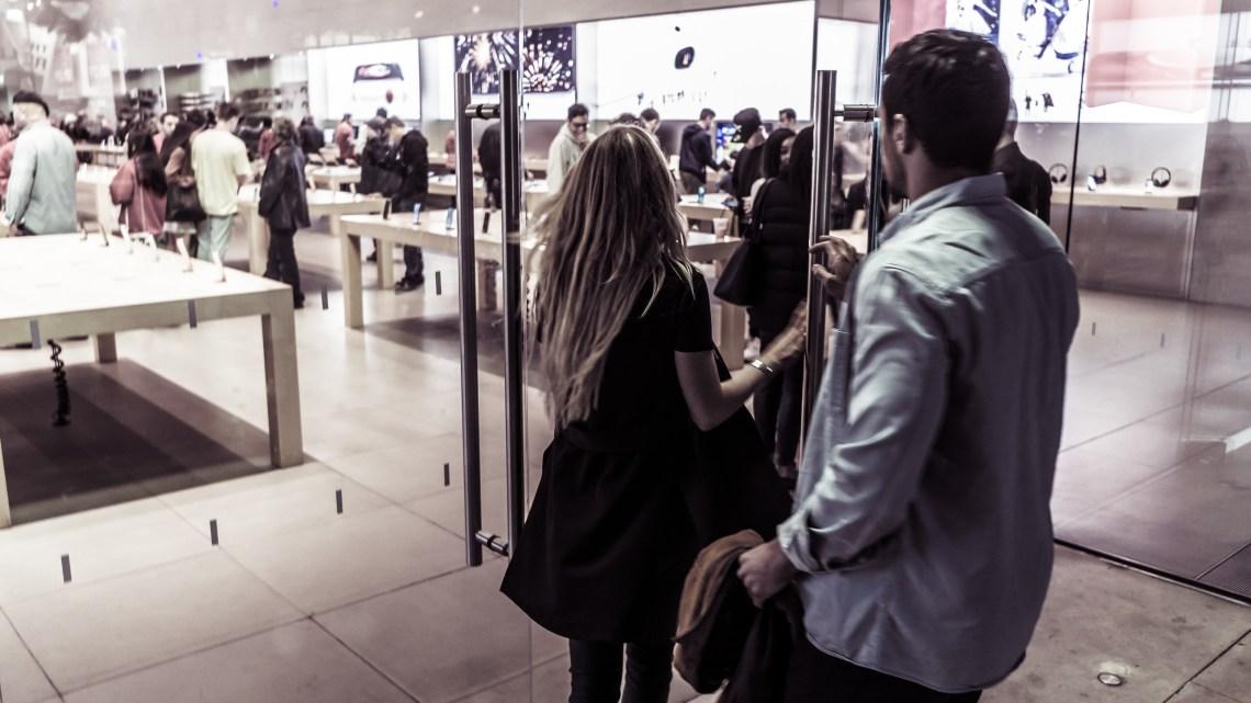 a couple walking into the Apple Store on the 3rd Street Promenade in Santa Monica California.