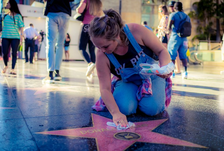a woman on her knees cleaning Donald Trump's Star on Hollywood Blvd