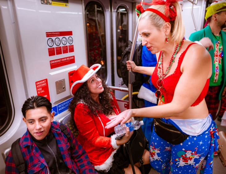 """A woman dressed for Santacon 2018 rides the Metro Gold line and lectures a young man that he needs to """"Call his mother"""""""