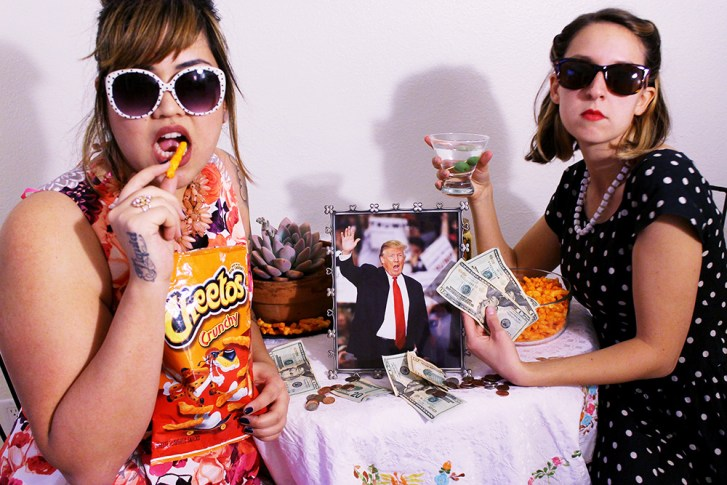 Alyssa Arney & Liz Flynn wearing big sunglasses at a table with a framed Donald Trump photo, stacks of US currency, and eating lots of Cheetos.
