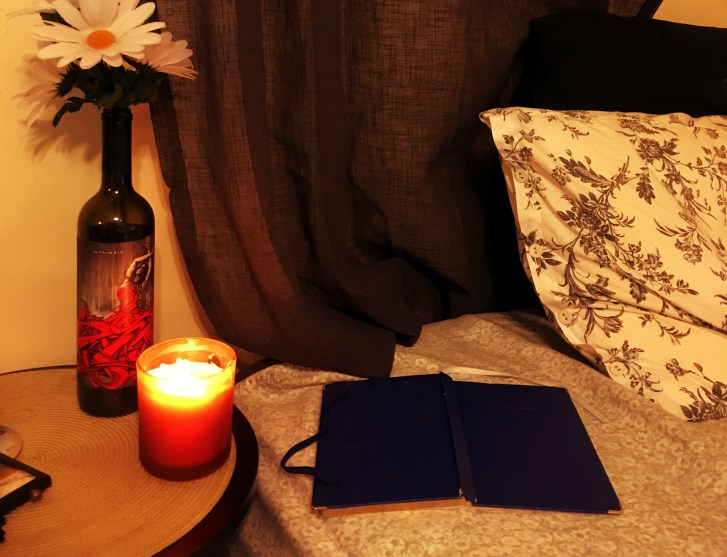 a book on a bed and a candle and flower on an adjacent nightstand