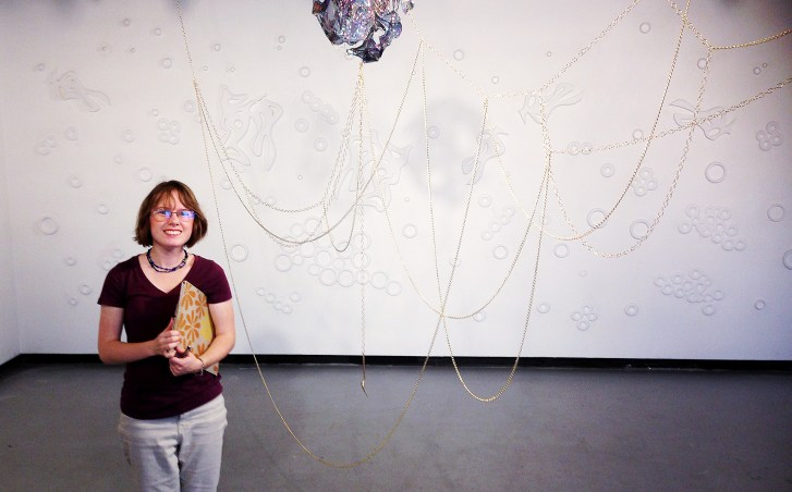 Hanna Adams stands in an installation featuring white on white bas relief geometric imagery
