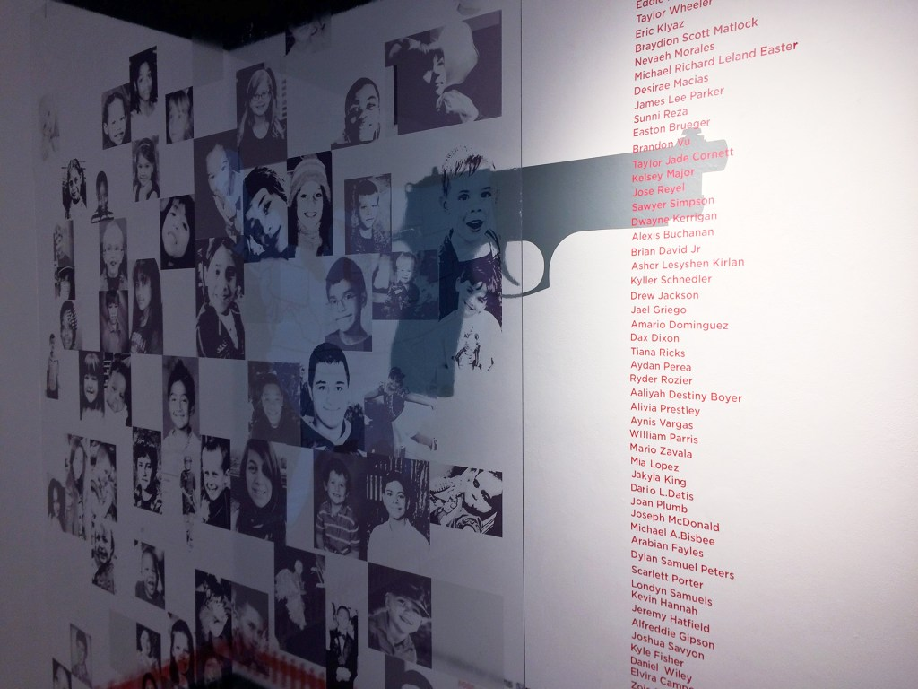a plexiglass sheet filled with many black and white pictures of children, next to a long running wall text listing the names of these children in red type, each of whom lost their life to gun violence in America