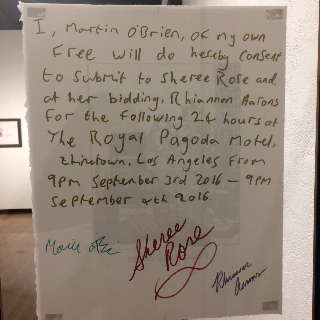 """photo of the back of a print from the Philosophy in the Bedroom performance. The handwritten text states, """"I, Martin O'Brien, of my own free will do hereby consent to submit to Sheree Rose and, at her bidding, Rhiannon Aarons for the following 24 hours at The Royal Pagoda Motel, Chinatown, Los Angeles from 9pm September 3rd 2016 - 9pm September 4th 2016. Under the handwritten text the print is signed by Martin O'Brien, Sheree Rose & Rhiannon Aarons"""