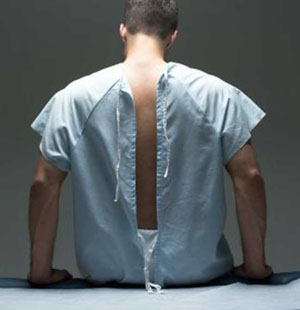 Man shown from behind in hospital gown