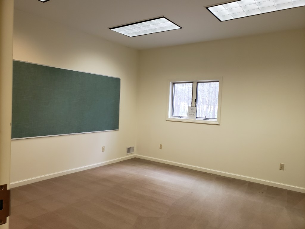 A room with white walls, a small window, tan carpeting, and a large green bulletin board on one wall.