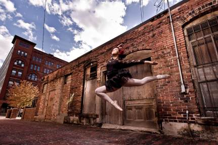 High school ballerina leaps in downtown Grand Rapids senior portrait photography