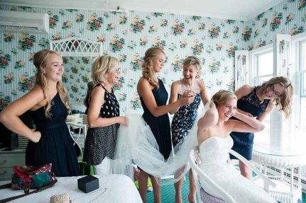 A Michigan bride laughs as her bridesmaids fasten the veil in her hair