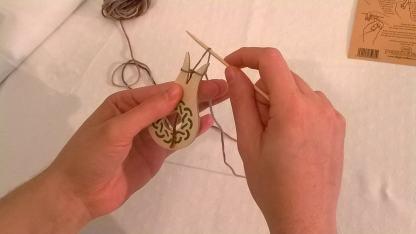 7) Sollevala fino a farla passare sopra il filo e sopra il dentino, verso il centro della forcella