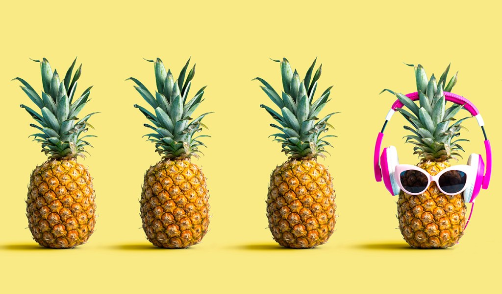 Several pineapples in a row that look the same, except the second to last pineapple from the right which has headphones and sunglasses