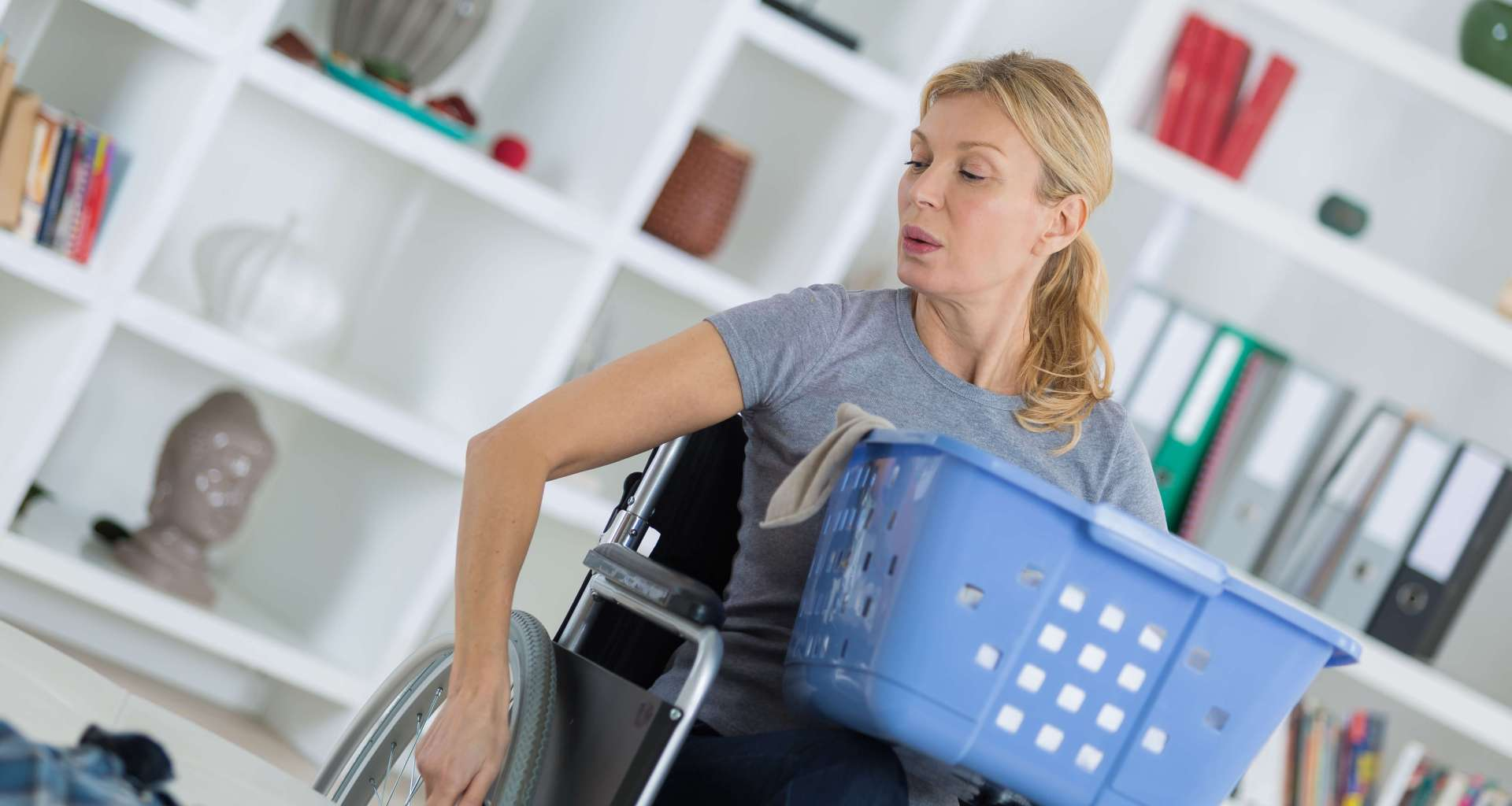Blonde woman in wheelchair carrying a laundry basket