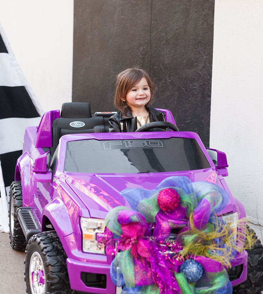 A little girl riding an F150 from Walmart for a holiday gift guide.