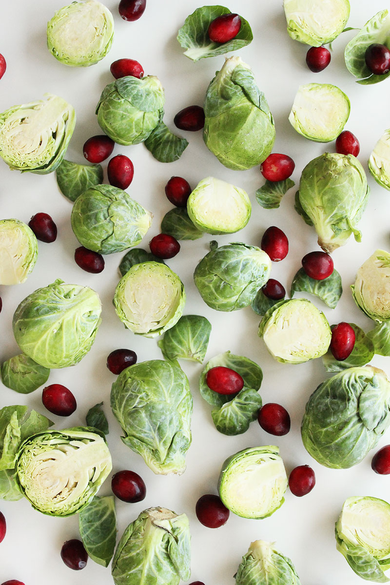 Cutting brussels sprouts in half to cook them with cranberries.