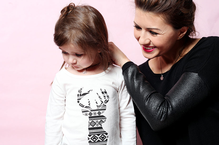 A mom in a leather shirt putting a Helen Ficalora charm necklace on her daughter.