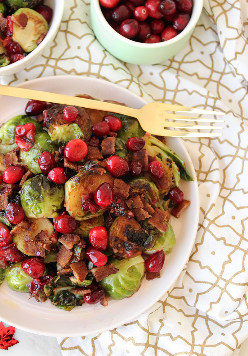 Brussels sprouts, bacon and cranberries on a pink plate with gold flatware and napkins.