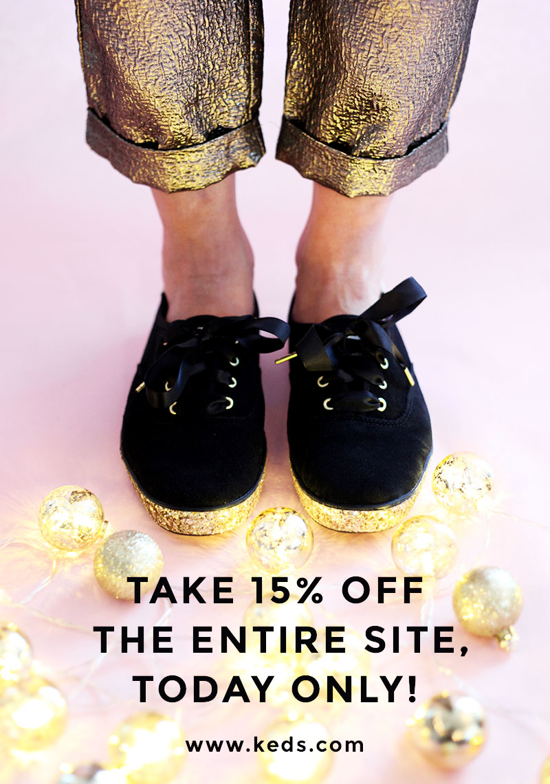 Black lace up Keds x Kade Spade sneakers with a gold platform bottom.