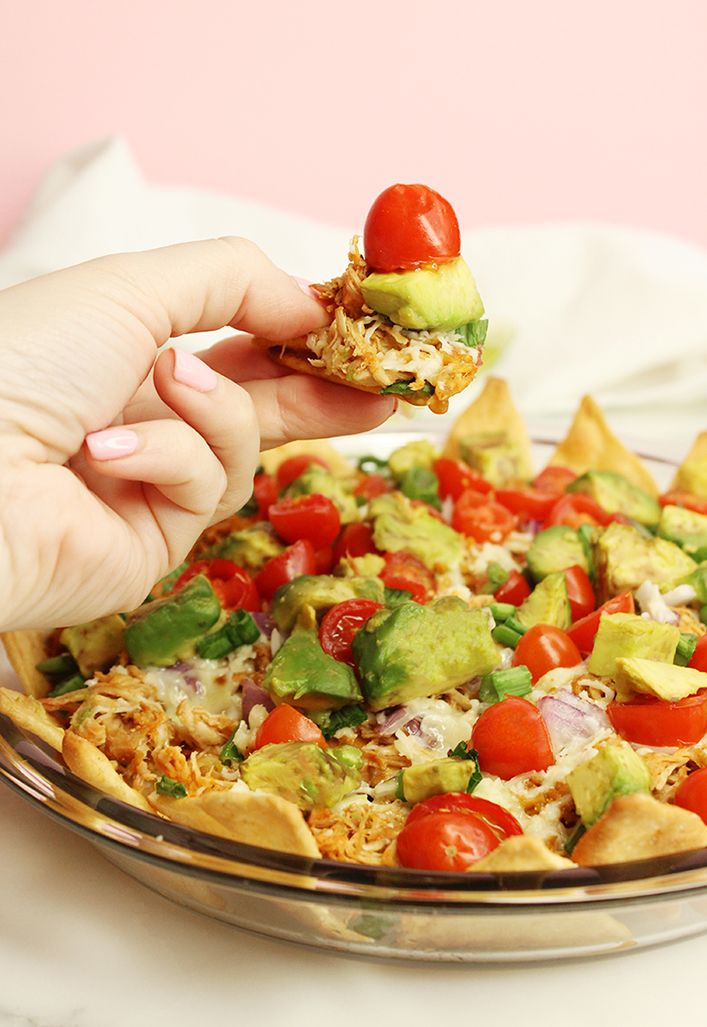 Eating pulled chicken nachos with avocados, cherry tomatoes, gruyere, onions and scallions.