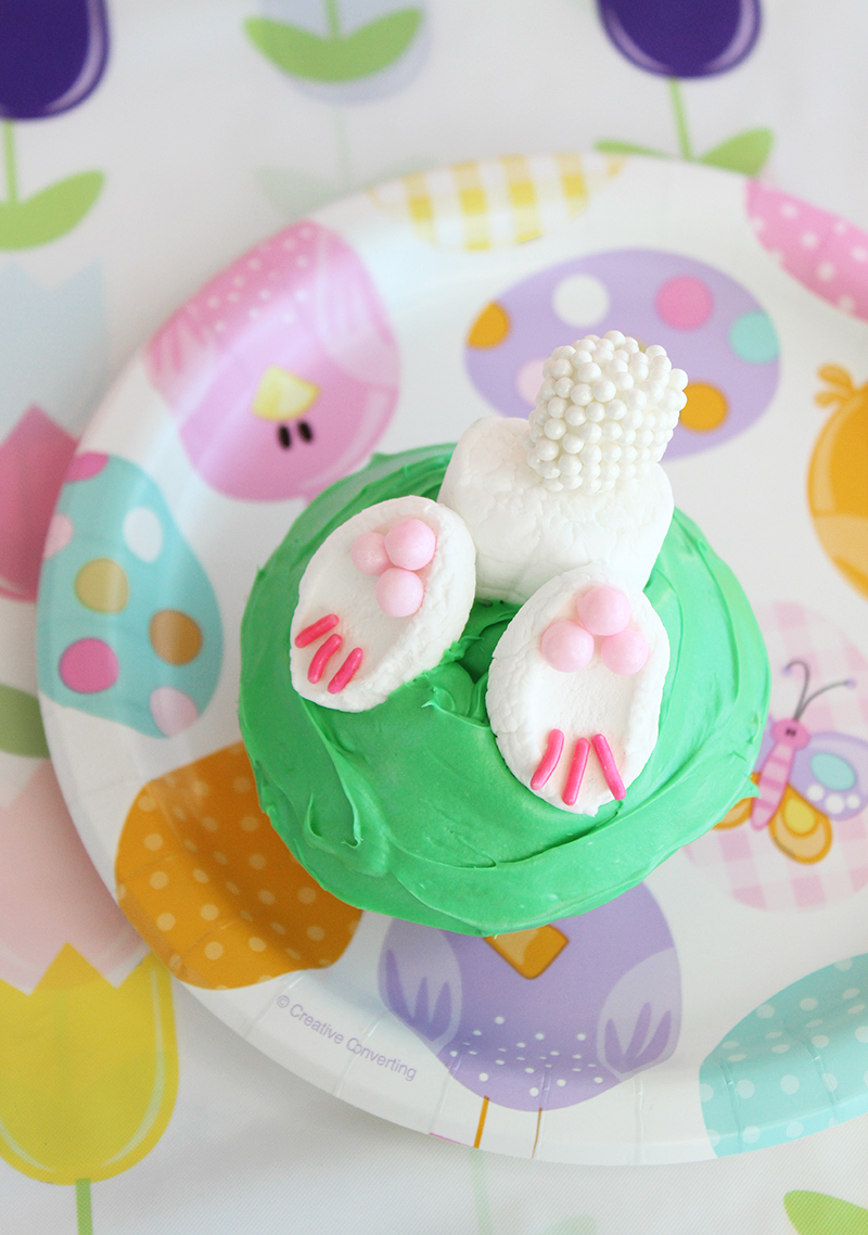 Bunny bottom Easter cupcakes with marshmallows and green frosting.