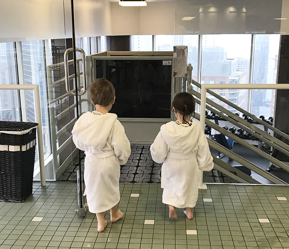 Two toddlers in white bathrobes going to the spa at the Swissotel.