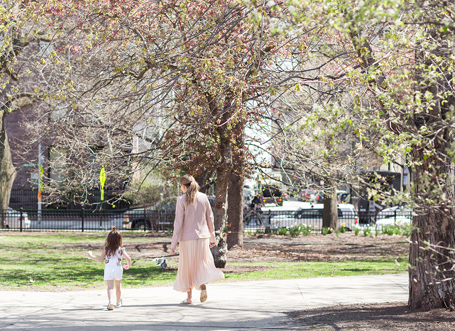 A mother daughter duo walking through the park.