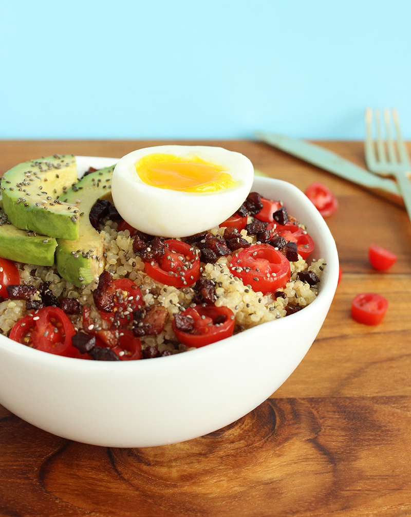 A savory breakfast bowl with soft boiled eggs, pancetta, avocado and cherry tomatoes.